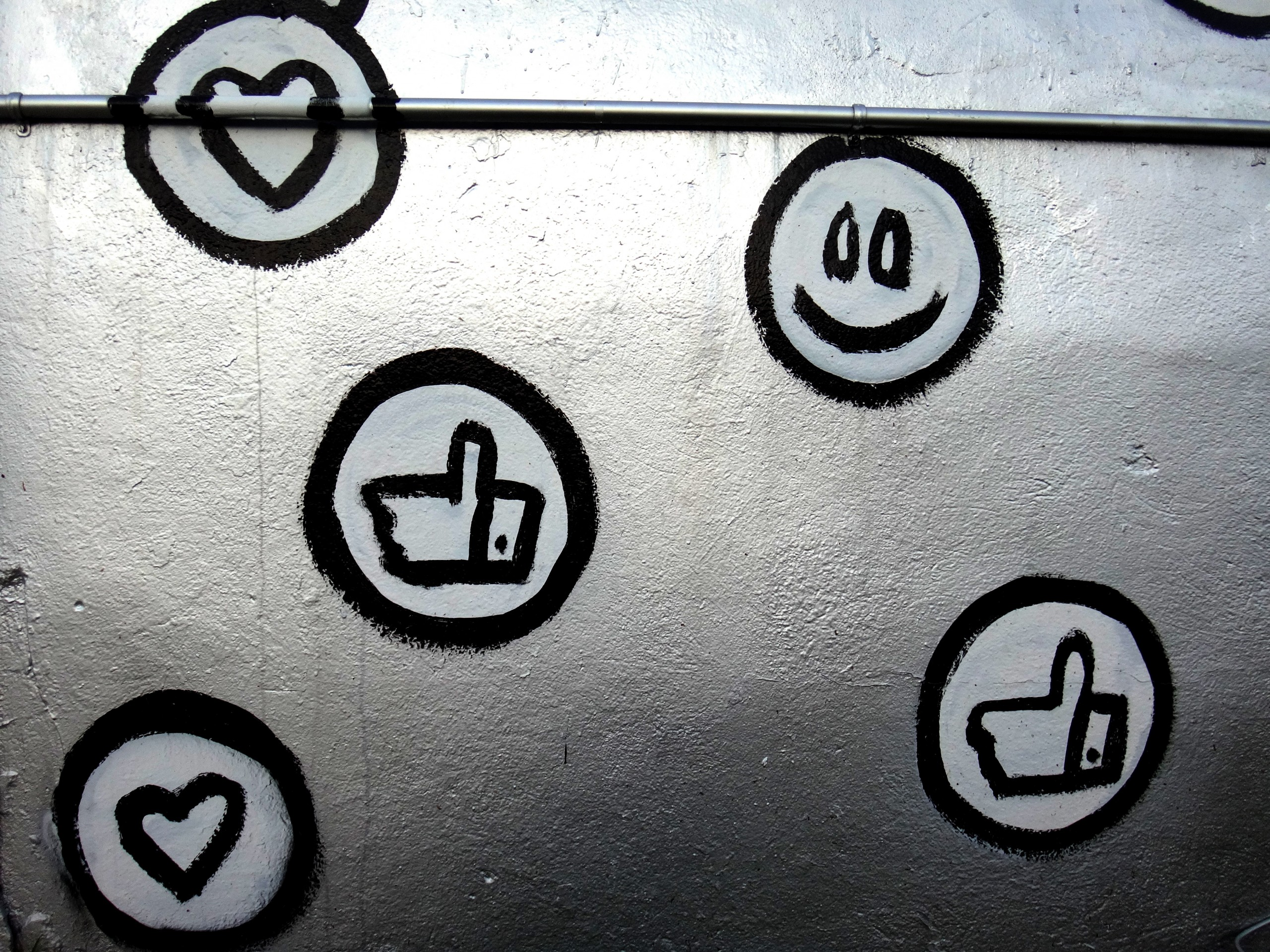wall with different symbols drawn on it such as smiley faces and thumbs up and love hearts
