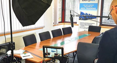 Man setting up to film conference room table